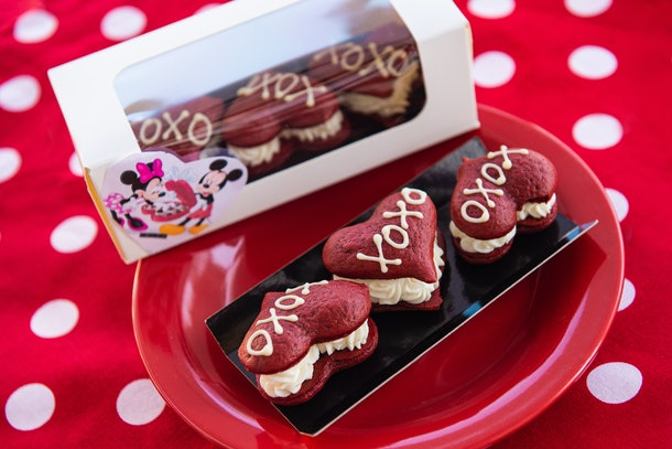 """Three red velvet whoopie pies with """"XOXO"""" written on them sit on a red plate for Valentine's Day at Disney."""