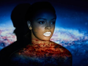 Young black woman in front of galaxy, universe background