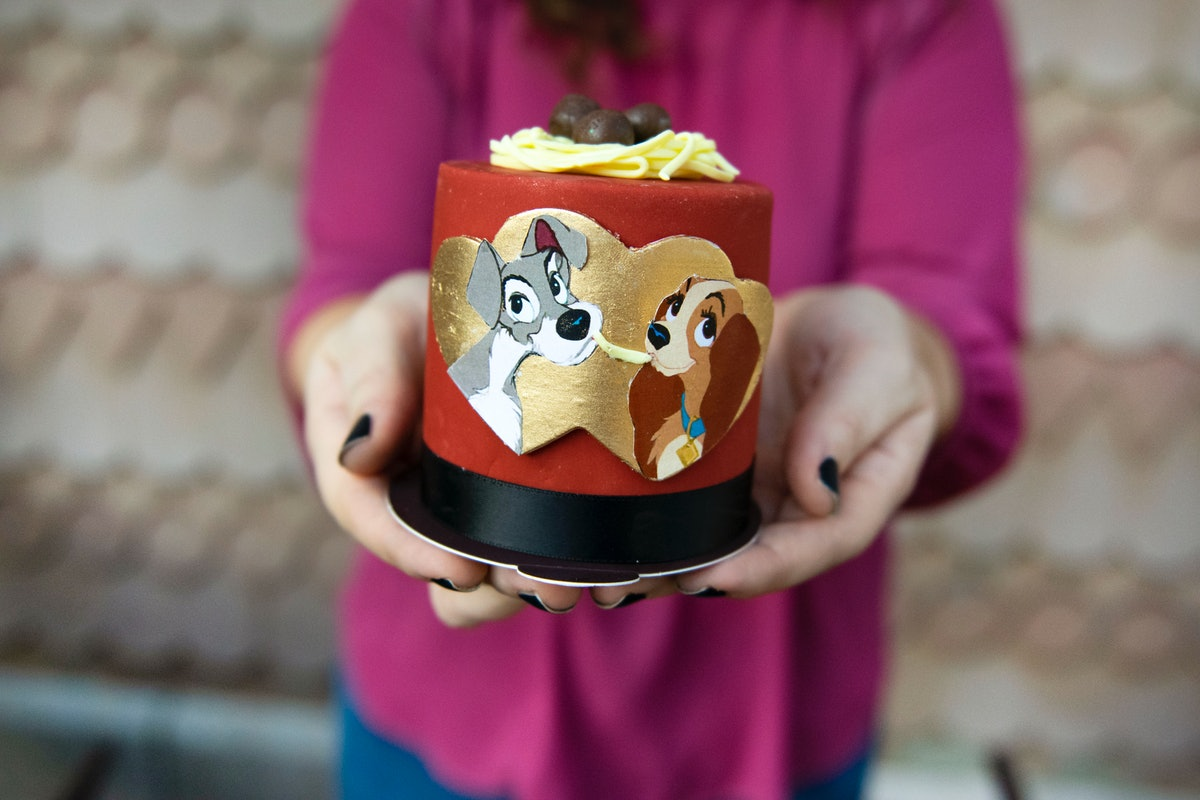 A woman holds out a 'Lady and the Tramp' cake for Valentine's Day at Disney.