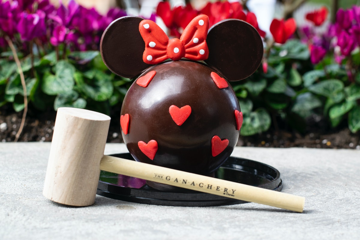 A Minnie Mouse-shaped chocolate piñata sits on the table with a wooden mallet for Valentine's Day at...