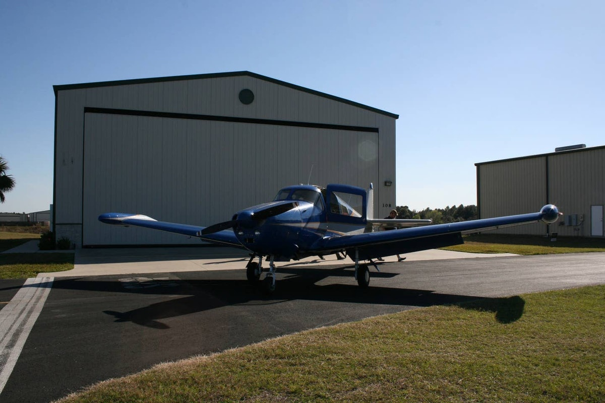 An airplane sits out in front of an airplane hangar available for rent on Airbnb.