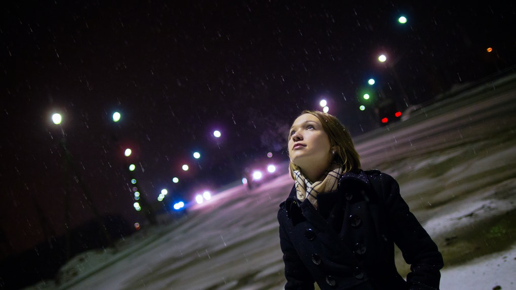 Young woman looking up at moon, night sky