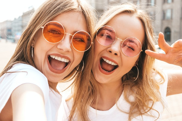Two women wearing circular-shaped sunglasses and white T-shirts smile and snap a selfie.