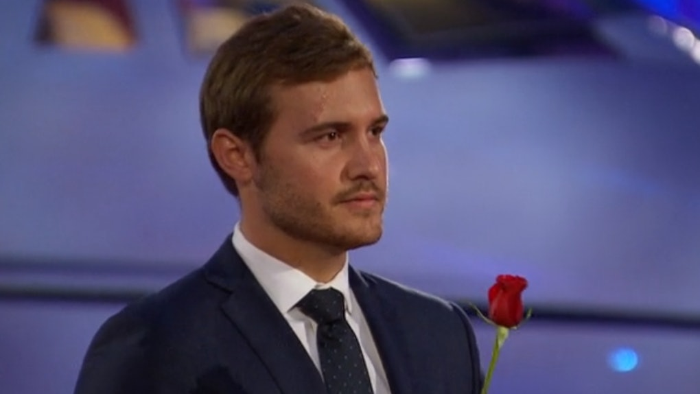 Pilot Pete from 'The Bachelor' holds a rose to hand out in front of an airplane.
