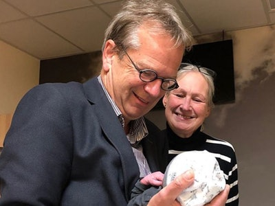 A man and woman, first-time grandparents, smile down at their newborn grandchild.
