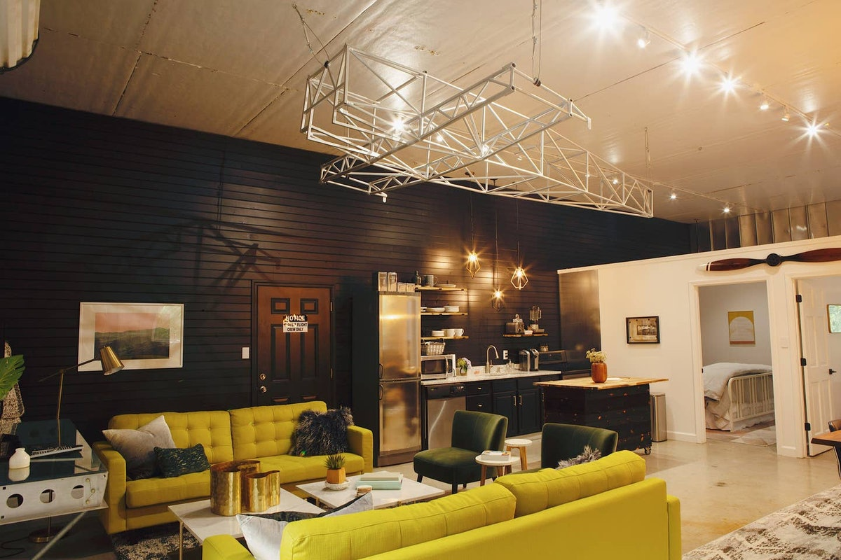 The interior of a hangar listed on Airbnb has bright yellow couches, green velvet chars, a black wall, and white and black kitchen appliances.