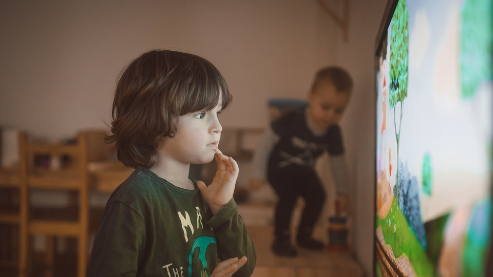 Child stands very close to television