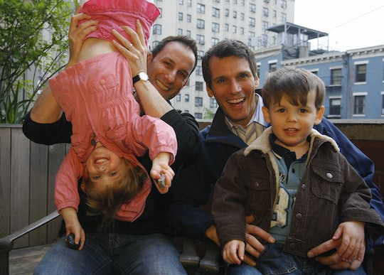 Two dads play with their kids, one dangled upsidedown