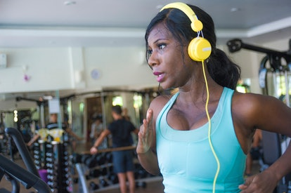A person with yellow headphones in a blue tank top runs on a treadmill. There is nothing wrong with modifying your exercises to fit your own body's needs at the gym.