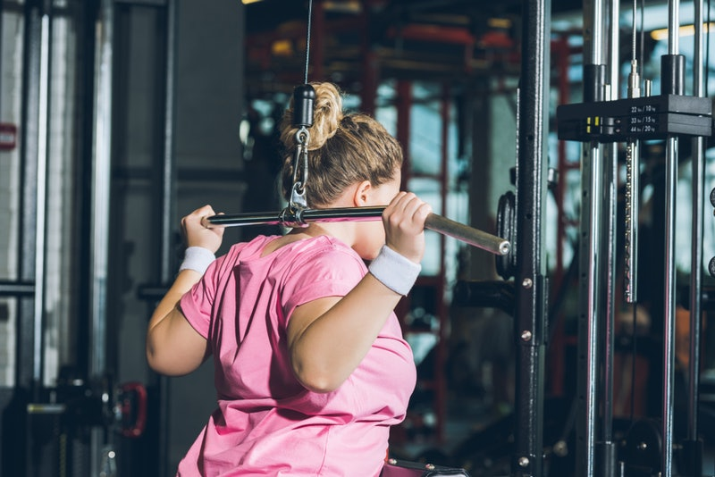 A person wearing a pink t-shirt and white wrist bands performs a lat pulldown behind her head. Gym anxiety may be keeping you from feeling comfortable in the gym, but there are ways to overcome it so you can have a great workout.