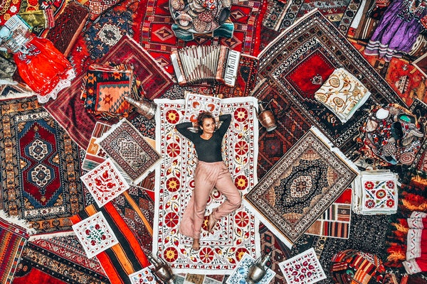 A woman lounges on a bunch of colorful rugs at a rug store in Cappadocia, Turkey.