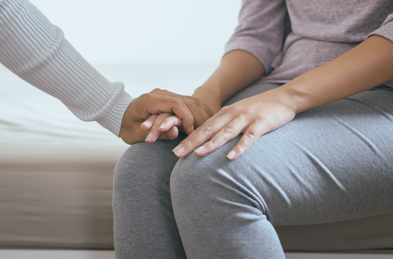 A woman holds an eating disorder patient's hand. OSFED, or eating disorders that fall outside the cl...