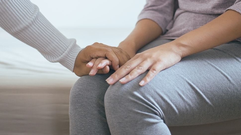 A woman holds an eating disorder patient's hand. OSFED, or eating disorders that fall outside the clinical definitions of other eating disorders, can risk not being taken seriously.