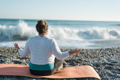 A person faces the ocean while meditating on a beach. You don't have to feel guilty when you miss a workout, experts say.