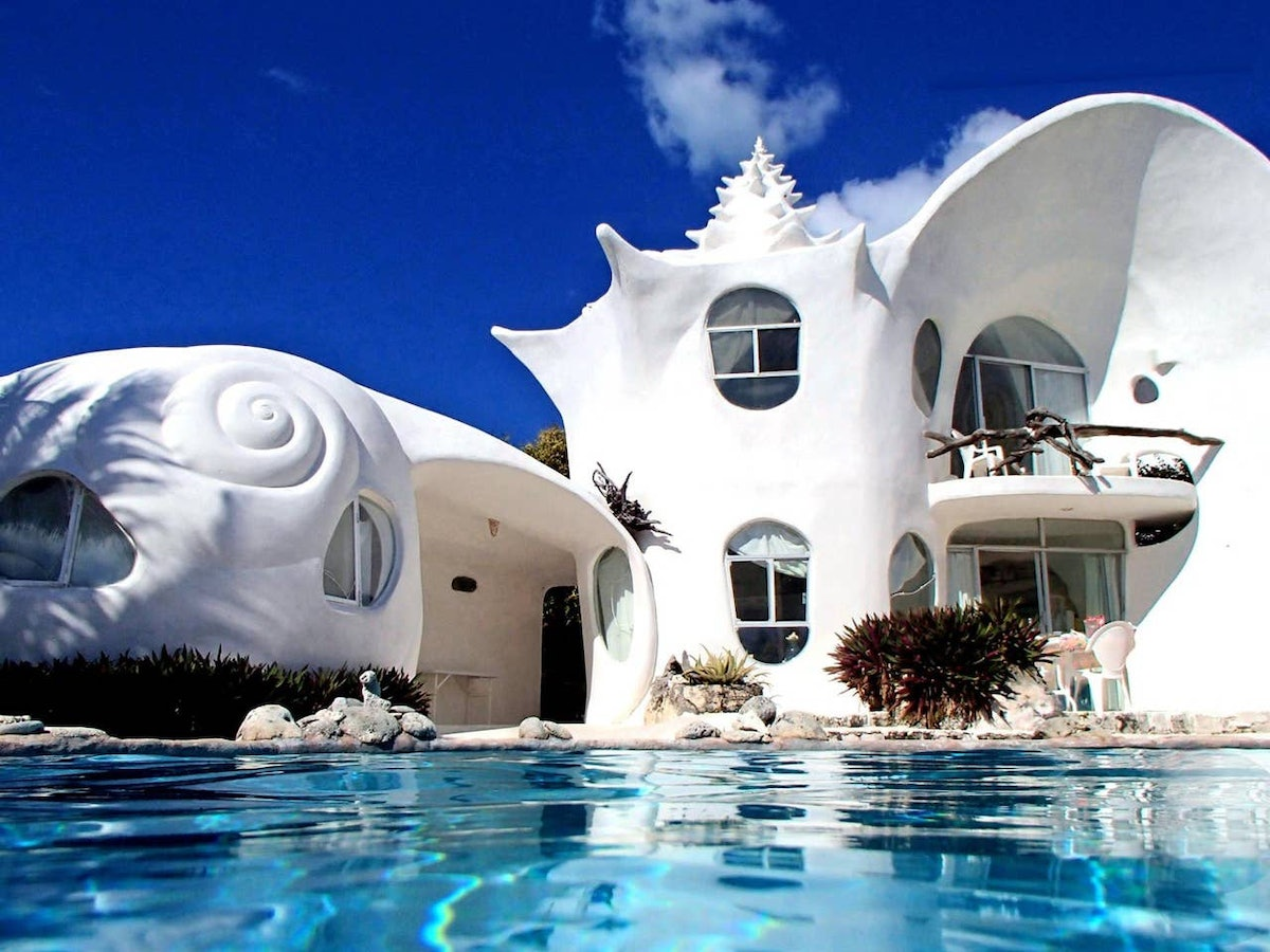The World Famous Seashell House on Airbnb has a dreamy pool and white exterior that's incredibly bri...
