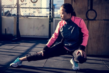 A person stretches her hamstrings and hips on the gym floor. If you're feeling guilty for missing a workout, it might be helpful to be extra gentle with yourself so you don't feel guilty about feeling guilty.
