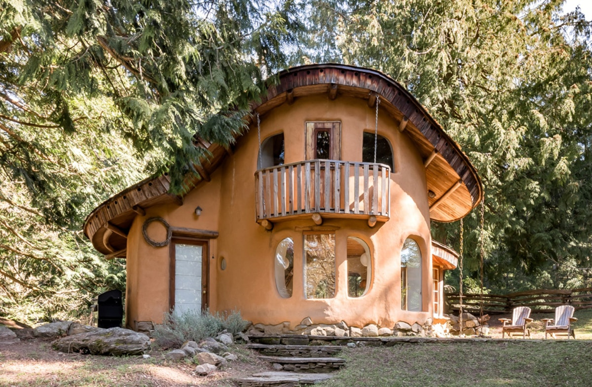 An orange cottage on Mayne Island is tucked into the woods and a short walking distance away from th...