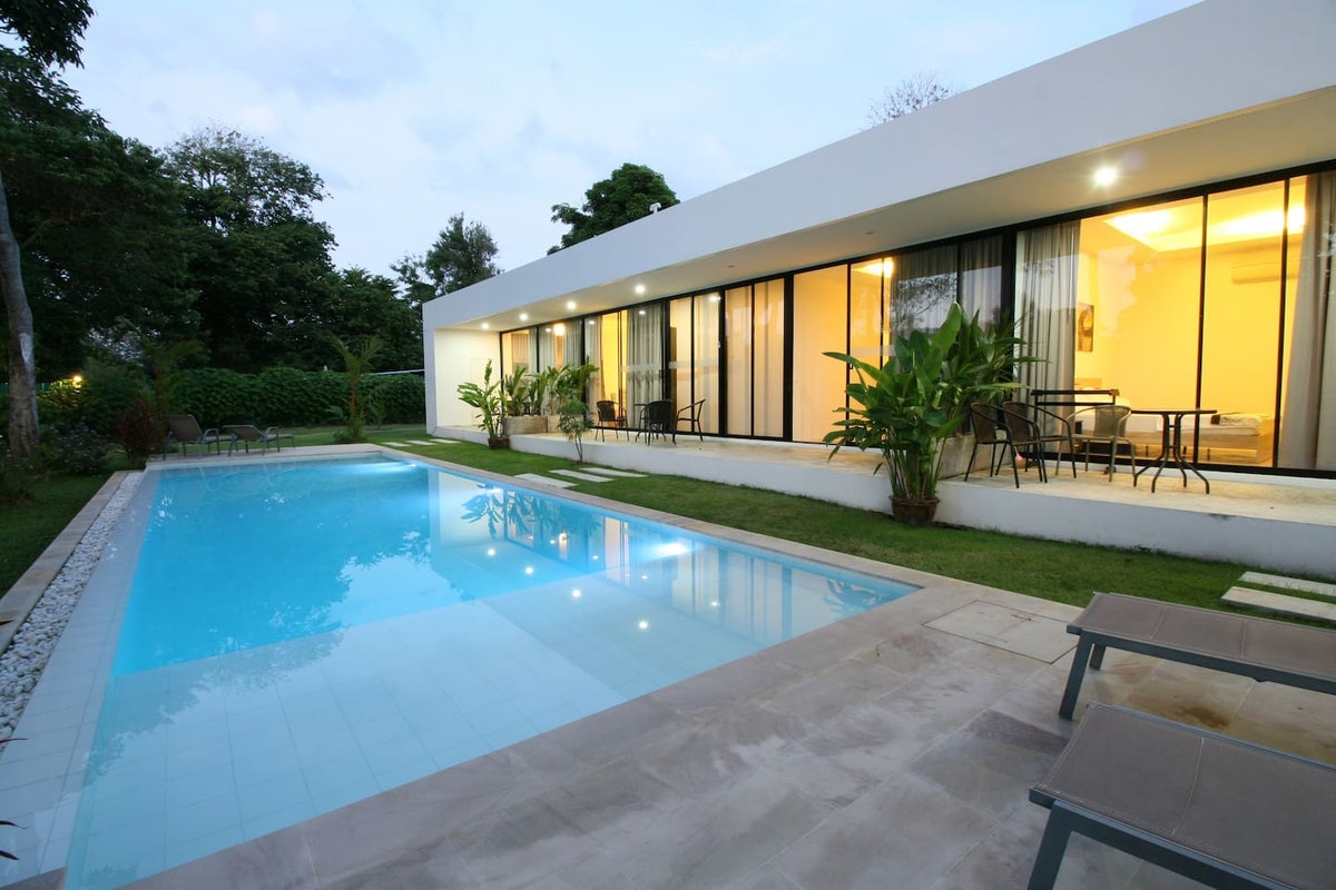 A modern apartment in Phuket, Thailand has a picturesque pool and large windows that overlook a porc...