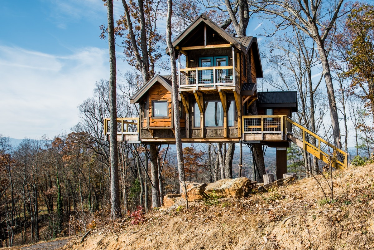 A two-story treehouse in North Carolina is surrounded by trees and available to rent on Airbnb.