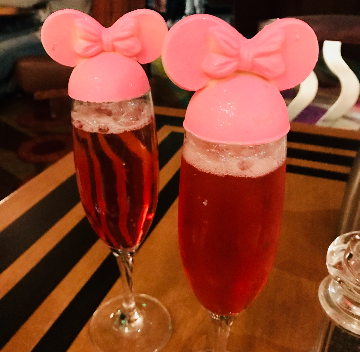 Two pink glittery mimosas with Minnie Mouse toppers are placed on a wood table at The Wave at Disney...