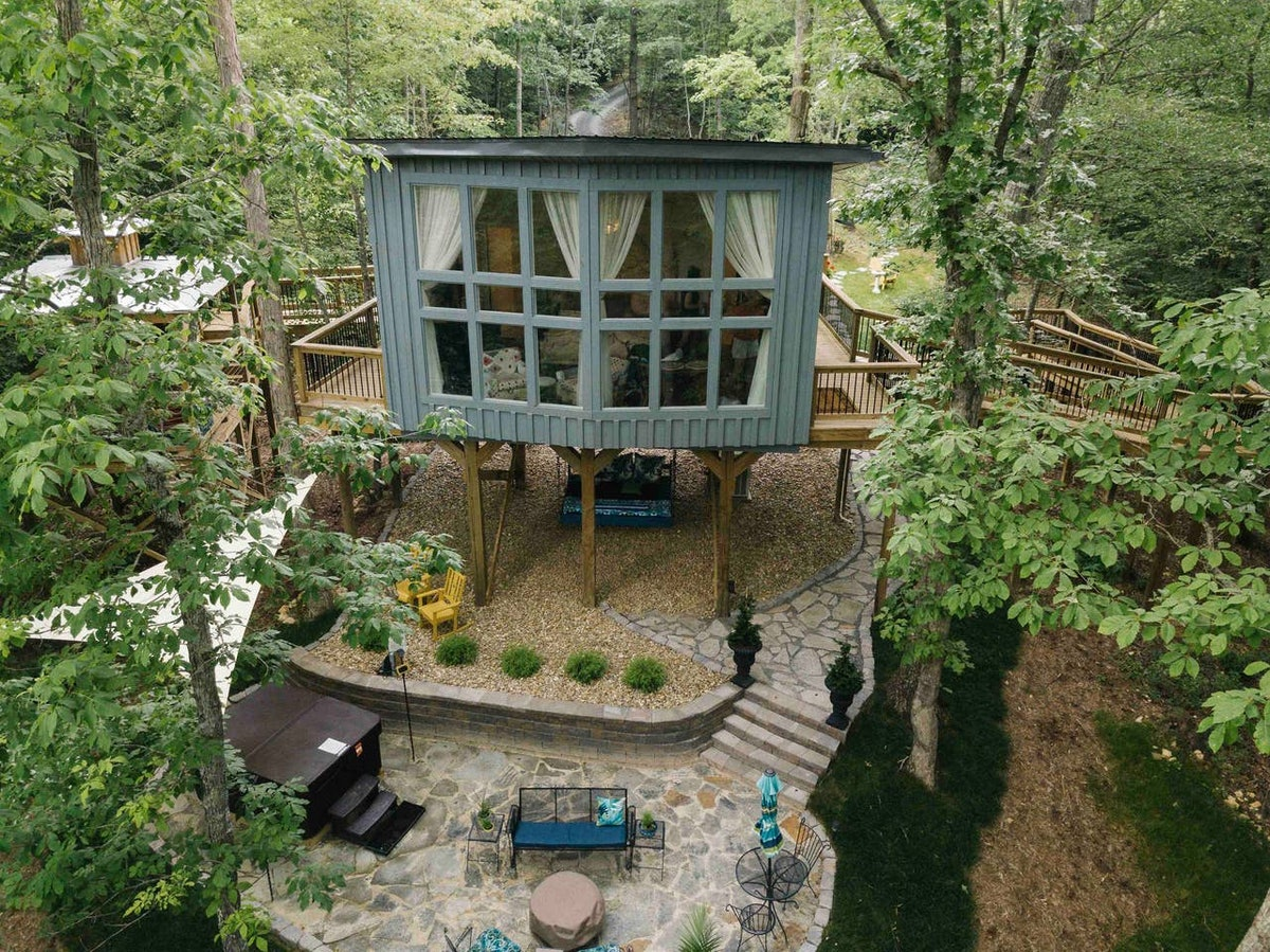 This treehouse in Tennessee has a large window, patio with a hot tub, and is available to rent on Ai...