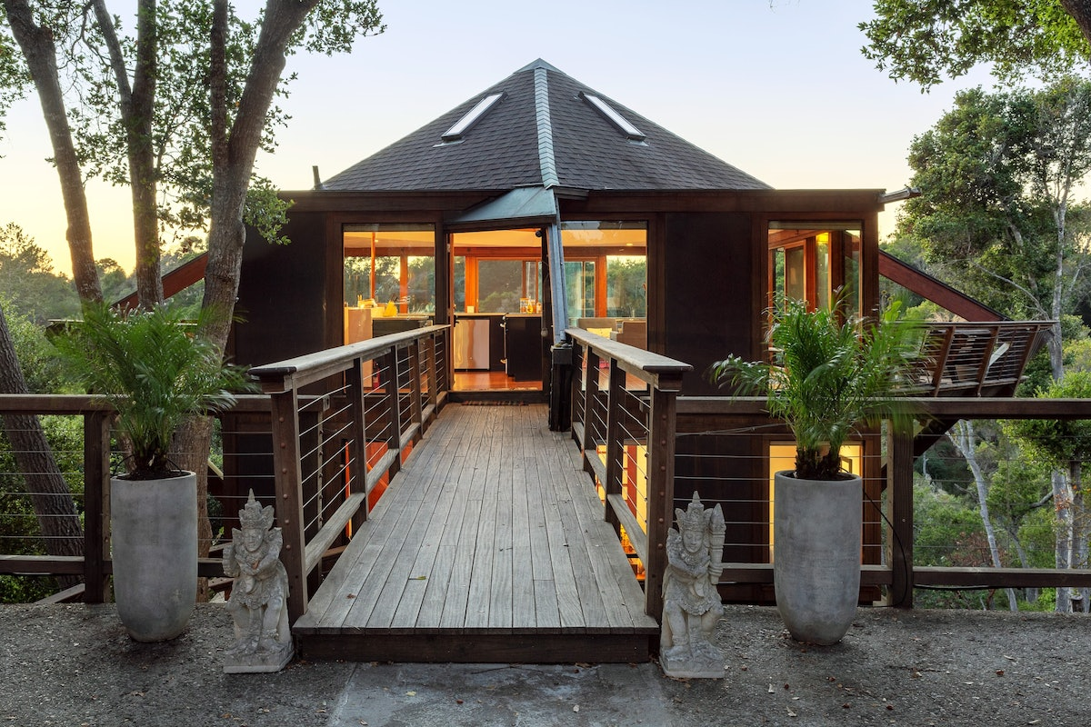 The front entrance of this Airbnb treehouse in California has a wooden bridge.