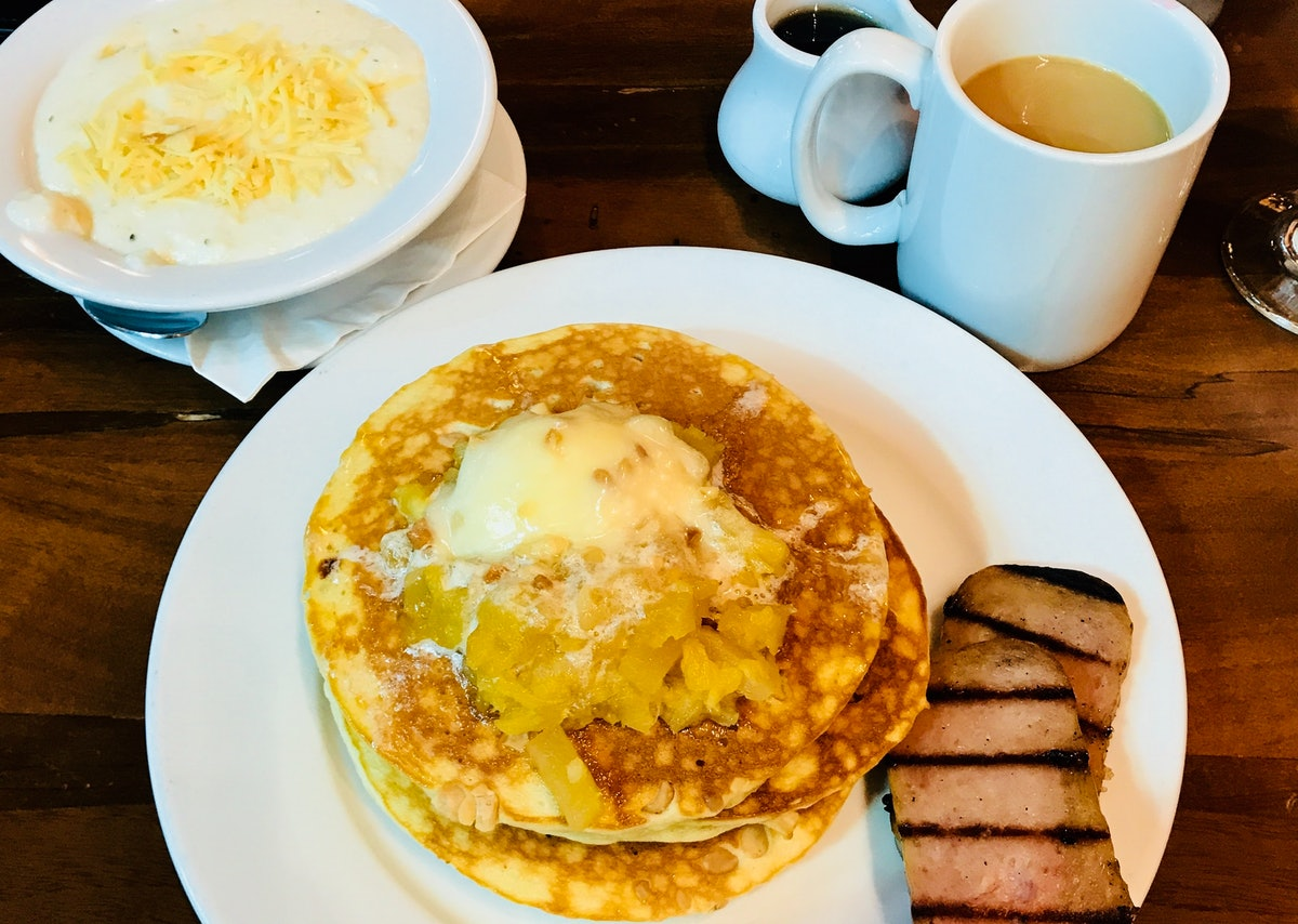 A plate of macadamia nut pancakes with pineapple and spiced ham is placed next to Kona coffee and gr...