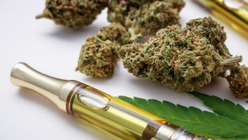 Marijuana buds closeup with cannabis oil vape and leaf.