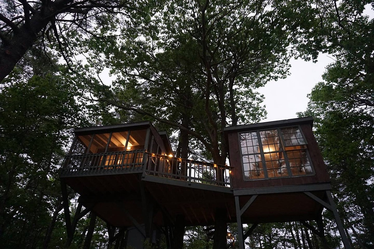 A treehouse that's available on Airbnb in Maine has two rooms and a deck, and is surrounded by trees...