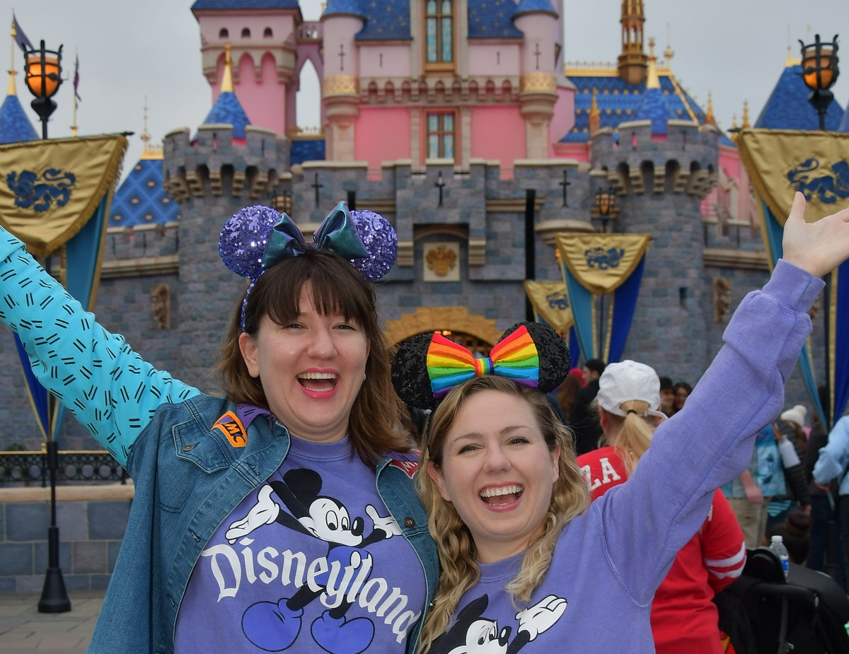 Two friends wearing matching purple Disneyland sweaters and Mickey ears stand in front of the castle...