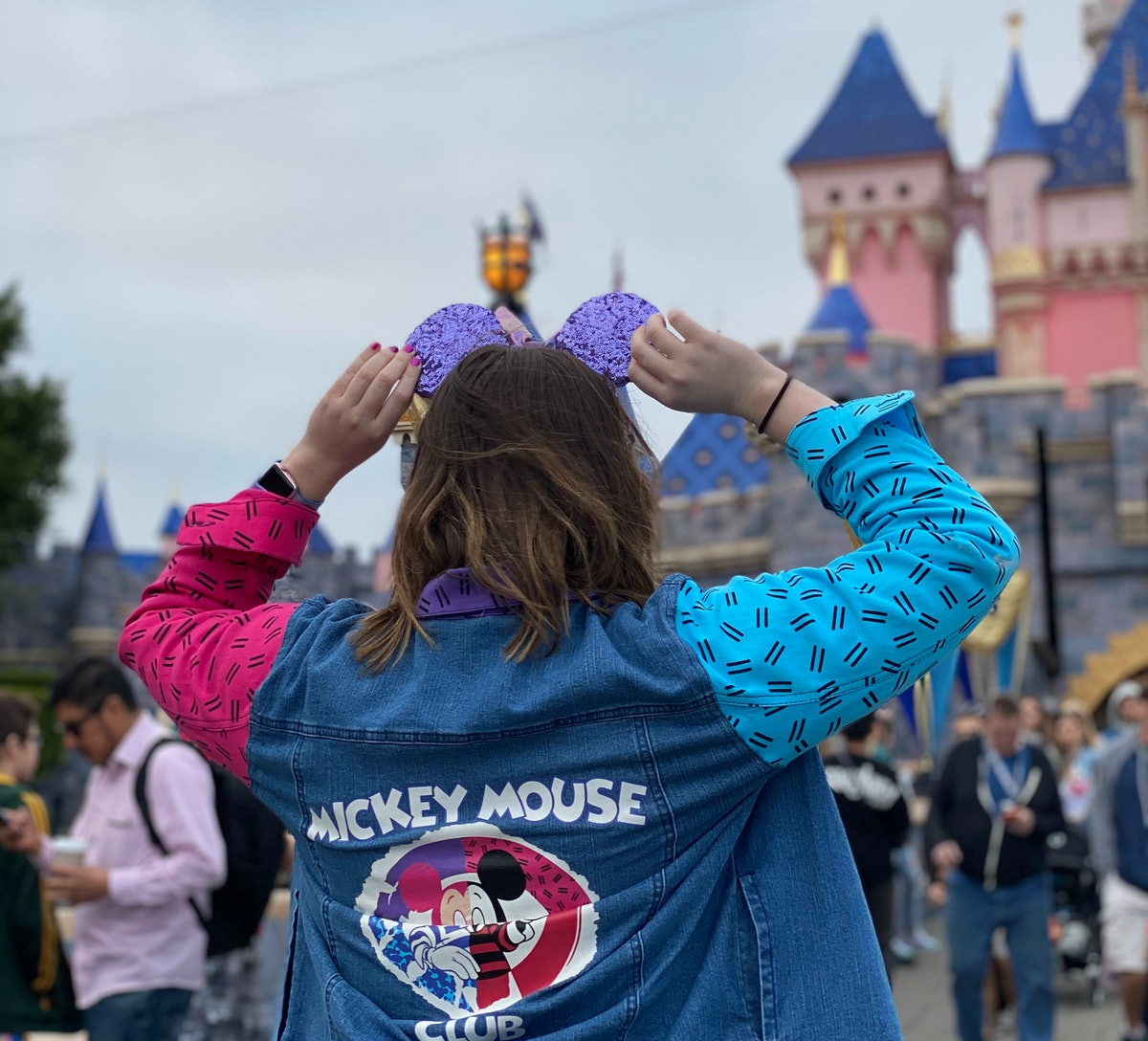 A woman holds her sparkly purple Mickey Mouse ears while standing in front of the castle at Disneyla...
