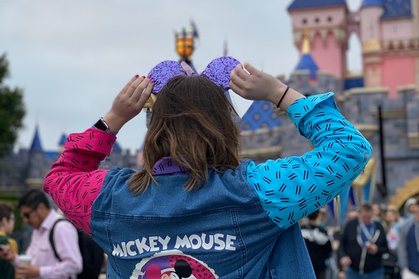 A woman holds her sparkly purple Mickey Mouse ears while standing in front of the castle at Disneyland.