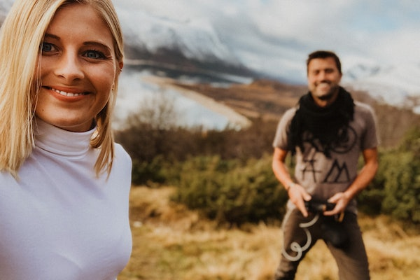 A blonde woman smiles while taking a selfie in a field with mountains in the background on a sunny day in Norway.