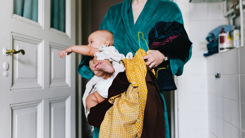 Woman holds baby and laundry pile