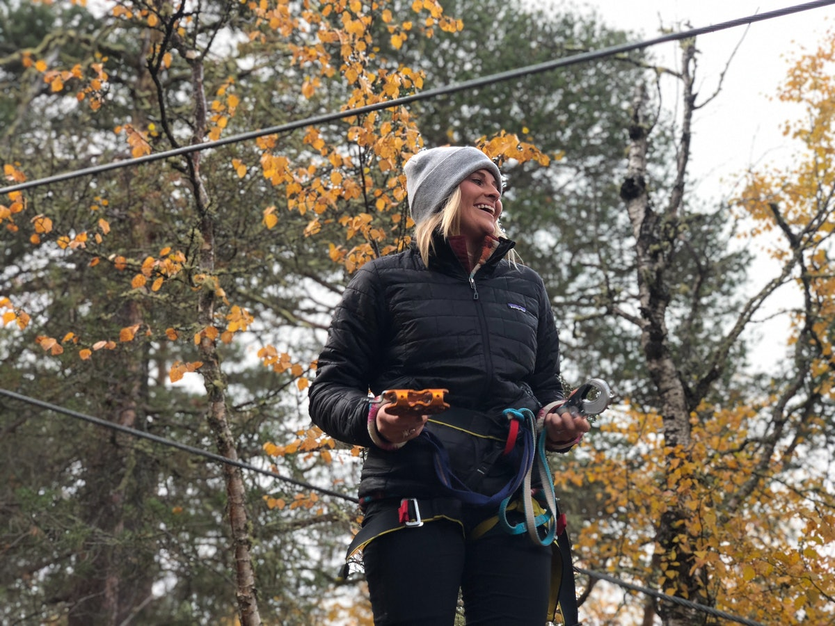 A woman dressed in a gray beanie, black jacket, and black leggings smiles on a fall day while gearin...