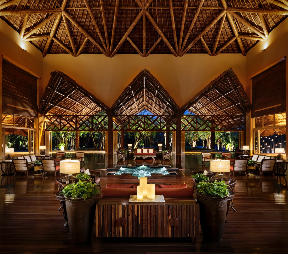 The lobby at Grand Velas Riviera Maya has an outdoorsy design and romantic atmosphere at night.