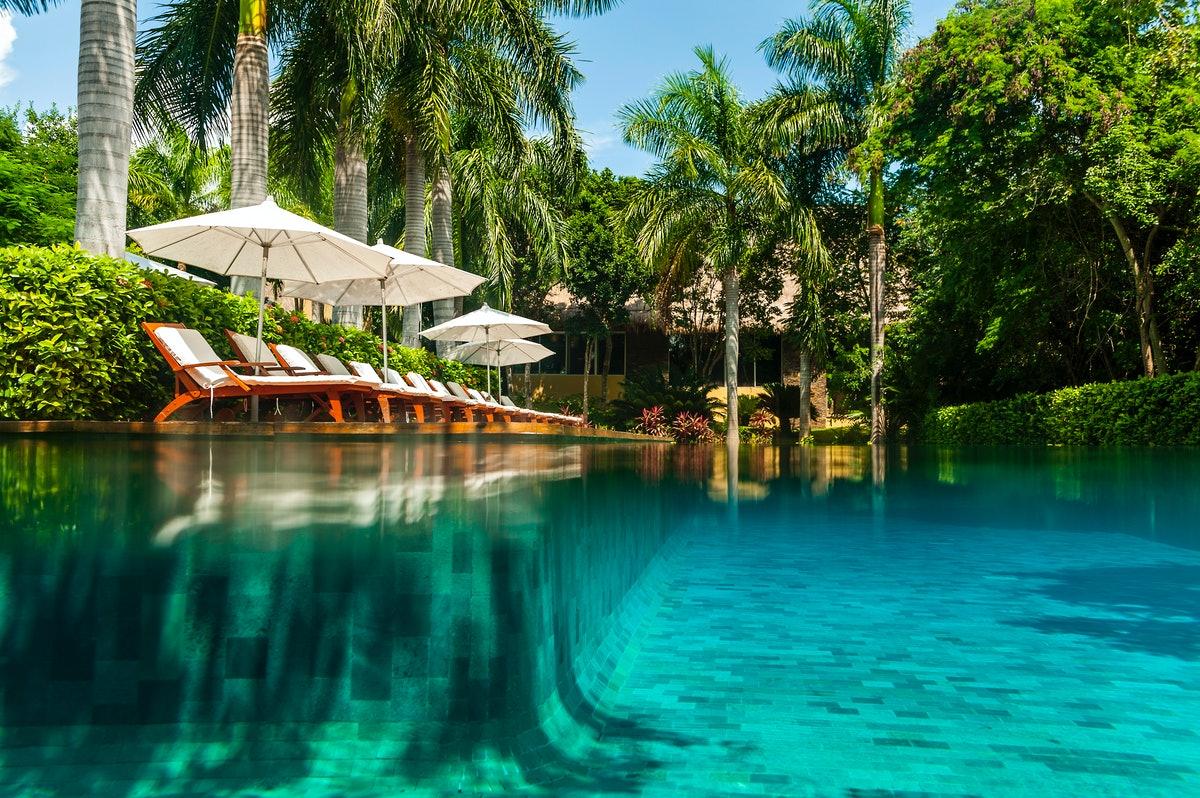 The pool at Grand Velas Riviera Maya features white lounge chairs with umbrellas and is surrounded b...