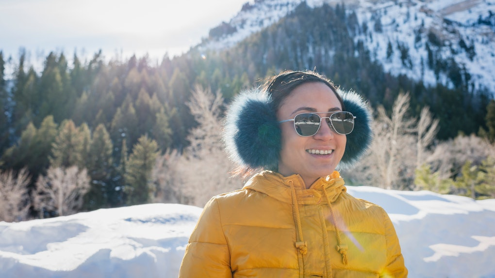 Young woman with earmuffs in snow