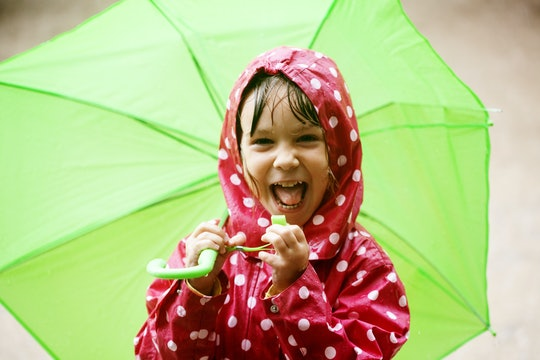 Smiling child in red raincoat with white polkadots holds a big green umbrella