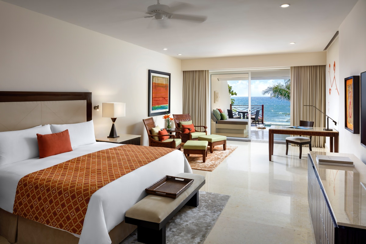A suite at Grand Velas Riviera Maya features a comfortable bed with orange and red accents, and a ba...