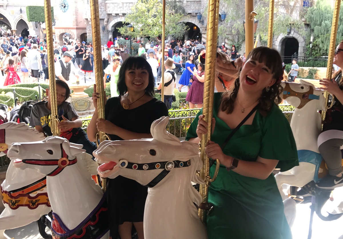 Two friends sit on horses at King Arthur Carousel in Disneyland.