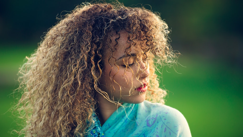 Curly-haired young woman outside
