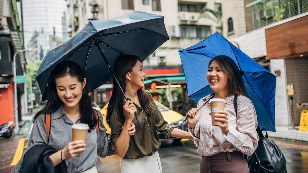 Three Asian female friends in the rain with umbrellas and coffee