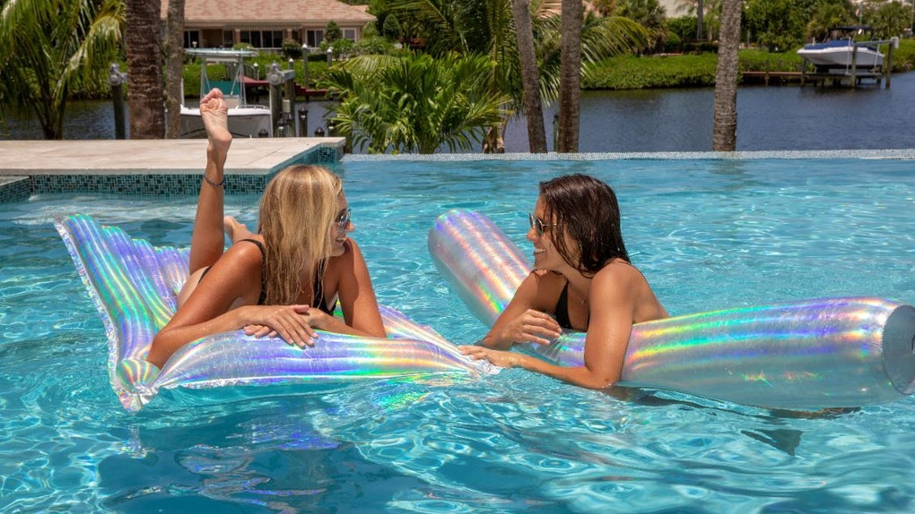 Two girls wearing swimsuits and sunglasses relax in the pool on their holographic floats from PoolCandy's collection.