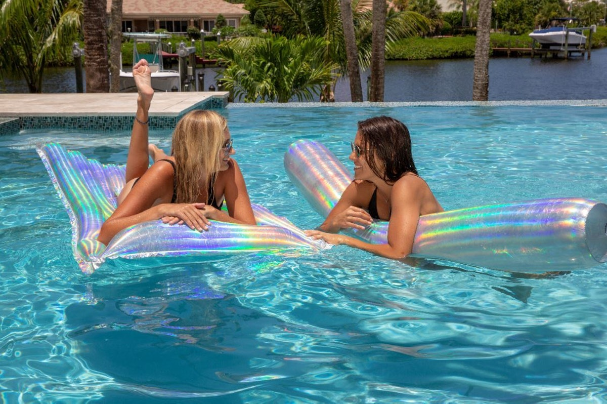 Two girls wearing swimsuits and sunglasses relax in the pool on their holographic floats from PoolCa...