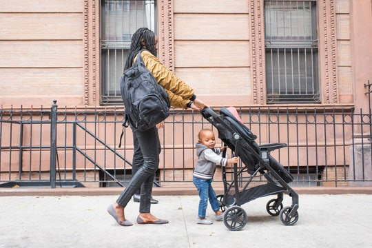 Mom pushing stroller, helped by toddler