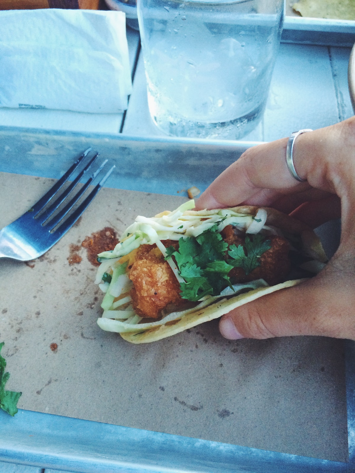 A woman holds a fish taco in her hand over a small, metal tray.