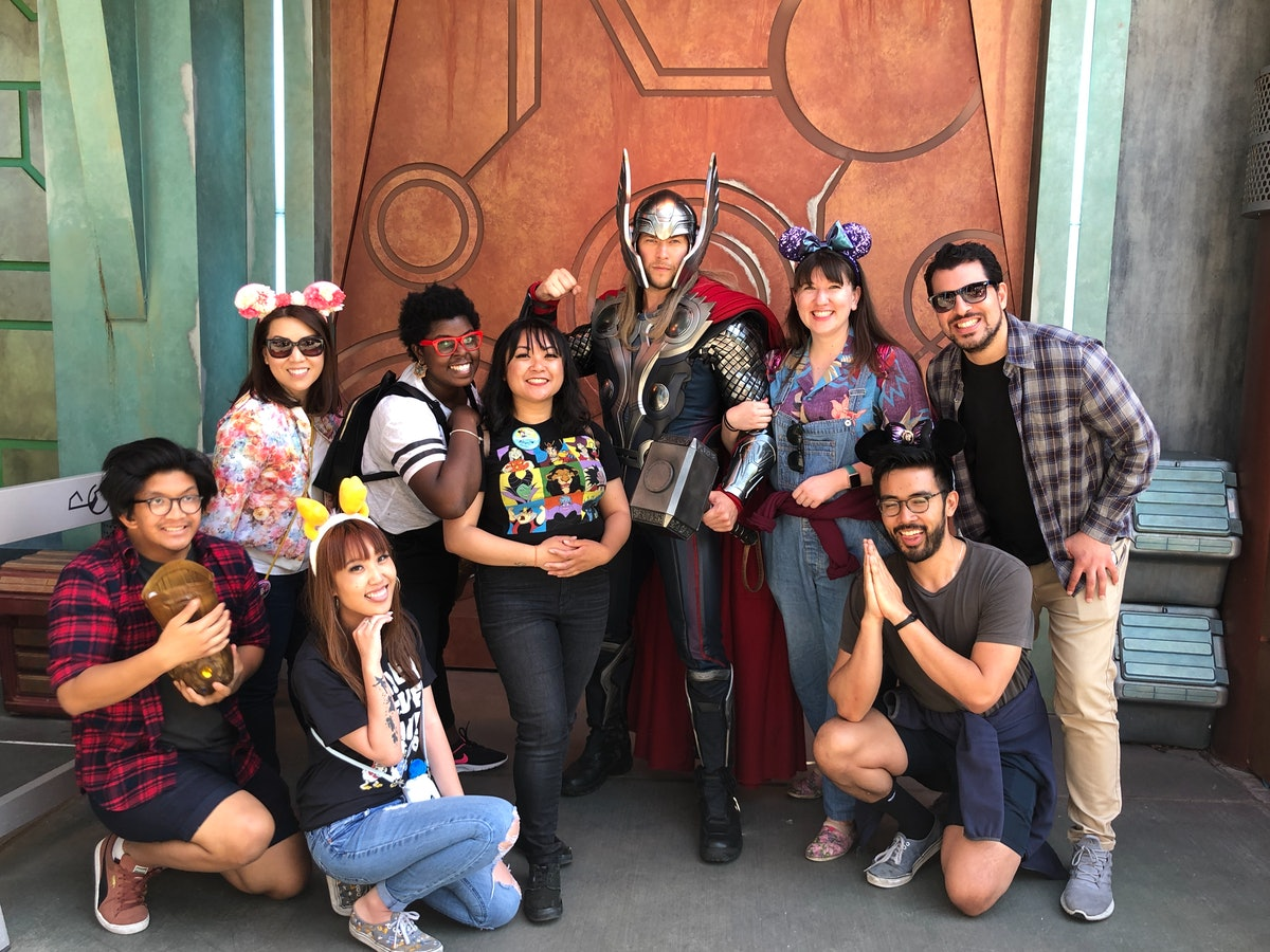 A big group of friends wearing Mickey Mouse ears pose and smile with Thor at Disneyland