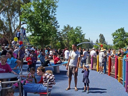 Children and parents play outside at a blue playground