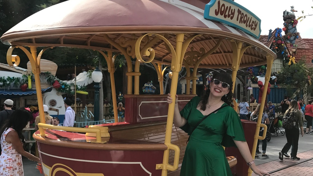 A woman in a long green dress and sunglasses smiles and poses on the trolley in Toontown at Disneyland on a sunny day.